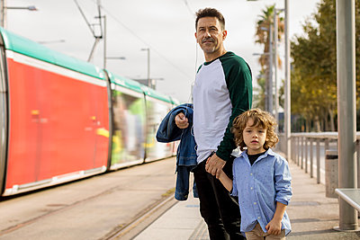 Father and son standing hand in hand at tram stop in the city - p300m2070412 von Mauro Grigollo
