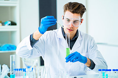 Young scientist mixing chemicals in graduated cylinder at laboratory - p300m2266133 by Giorgio Fochesato