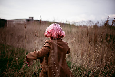 Caucasian woman with pink hair running in field - p555m1491640 by Aliaksandr Liulkovich