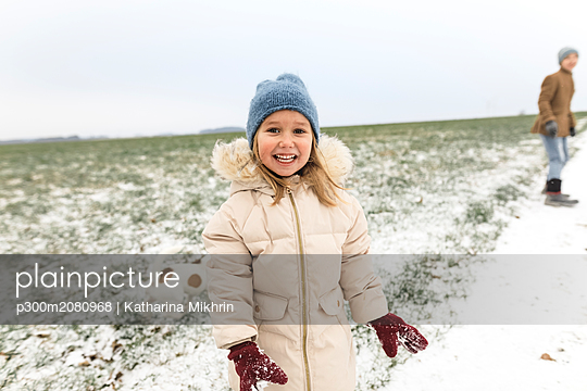Portrait of happy girl with dog and brother in winter landscape - p300m2080968 by Katharina Mikhrin