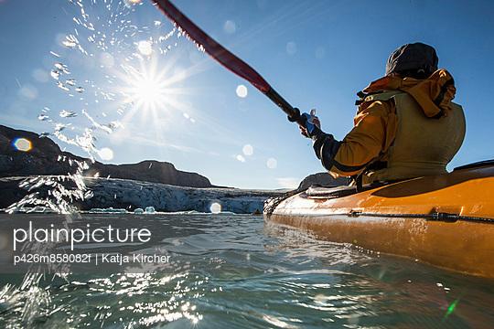 Rear view of mature woman kayaking on sea - p426m858082f by Katja Kircher