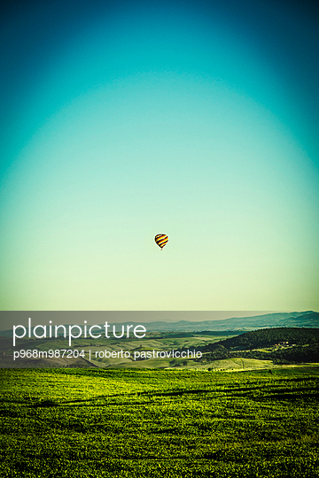 The Balloon flying in the morning over Tuscan hills - p968m987204 by roberto pastrovicchio