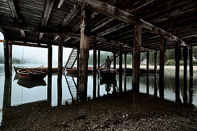 Man in white dress stands in a boat under the dock - p1383m1496364 by Wolfgang Steiner