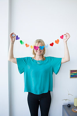 Caucasian woman covering eyes with string of paper hearts - p555m1303620 by verity jane smith