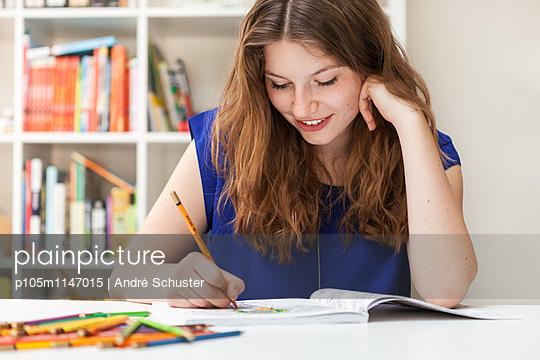 Junge Frau mit Ausmalbuch - p105m1147015 von André Schuster