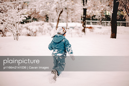 Rear view of boy running in snow covered field in park in winter - p1166m2141036 by Cavan Images