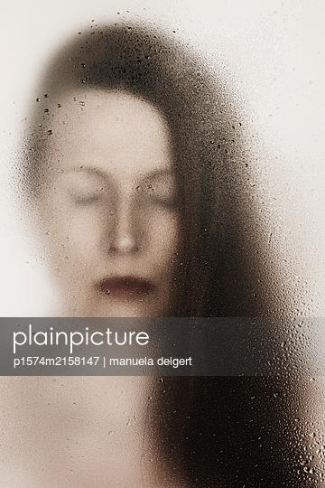 Portrait einer Frau mit geschlossenen Augen hinter einer Scheibe mit Wassertropfen - p1574m2158147 von manuela deigert