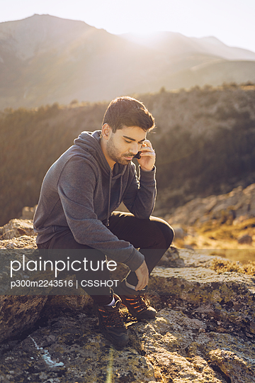 Young man talking over smart phone while sitting on mountain - p300m2243516 by CSSHOT