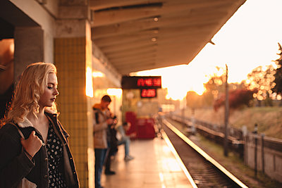 Young woman waiting for train at subway station during sunset - p1166m2153535 by Cavan Images