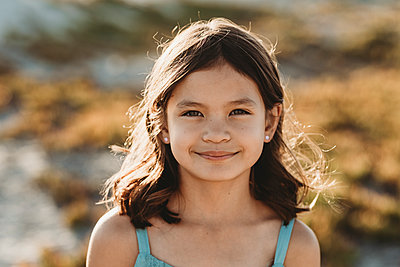 Smiling 8 yr old girl with sunlight playing through her dark hair - p1166m2207832 by Cavan Images