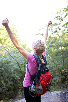 Young woman showing success after reaching the summit - p1166m2247058 by Cavan Images