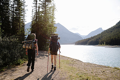 Female backpackers hiking along sunny lakeside - p1192m2129243 by Hero Images