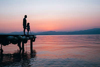 Italy, Lazise, father and little daughter standing on jetty looking at Lake Garda at sunset - p300m1469990 by Ina Peters
