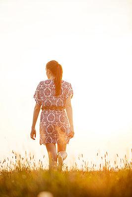 Young woman walking across a meadow in sunset - p300m2275387 by Jean Schwarz