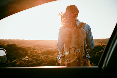 Female backpacker seen from car window during sunset - p300m2290477 by Eva Blanco