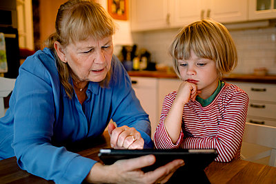 Boy looking at grandmother using digital tablet - p426m2195095 by Maskot