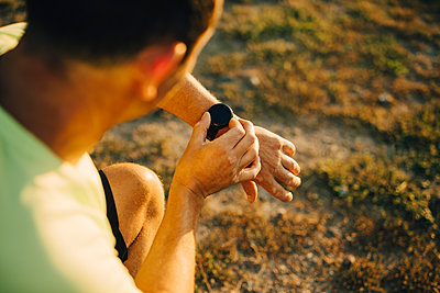 Cropped image of sportsman checking time on wristwatch - p426m2270559 by Maskot