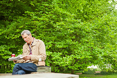Man reading newspaper in park - p429m659809f by Bill Sykes