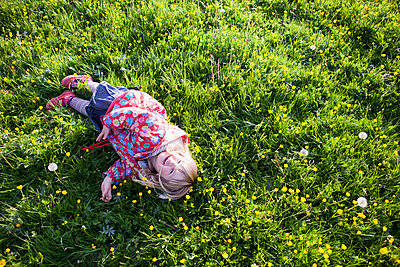 Girl rolls on the grass laughing - p505m1048187 by Iris Wolf