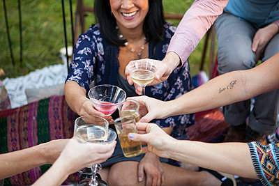 Friends toasting with champagne at picnic in park - p555m1409566 by Shestock