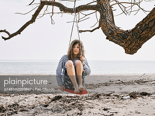 Girl sitting on a swing on beach, Sweden - p1481m2203847 by Peo Olsson