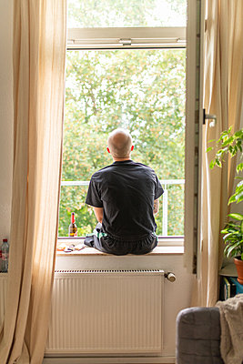 Man sitting on windowsill in his apartment - p1267m2258792 by Jörg Meier