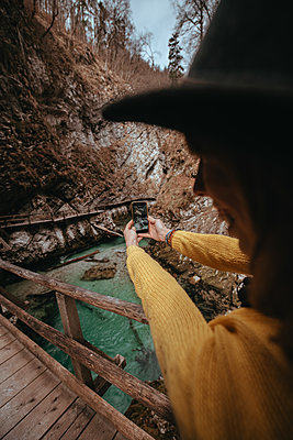 Woman taking a photo with her smartphone in the Vintgar Gorge in Slovenia - p1455m2081778 by Ingmar Wein