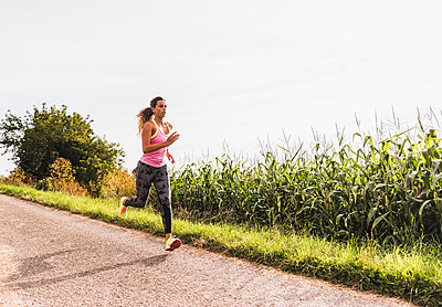 Young woman running on country lane - p300m1189258 by Uwe Umstätter