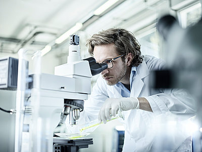 Laboratory technician looking through microscope in lab - p300m1550284 by Christian Vorhofer