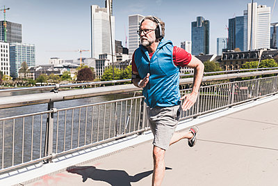 Mature man with headphones running on bridge in the city - p300m1587538 by Uwe Umstätter