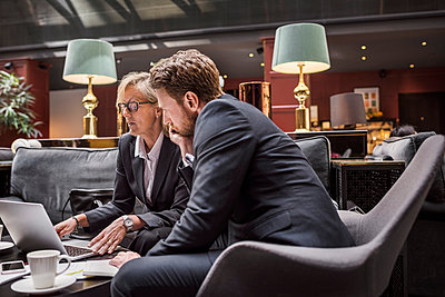 Business people discussing while looking at laptop in hotel reception - p426m1442737 by Maskot
