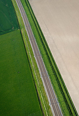 Aerial view of railway track through fields, Nieuwdijk, Zeeland, Netherlands - p429m1156210 by Mischa Keijser