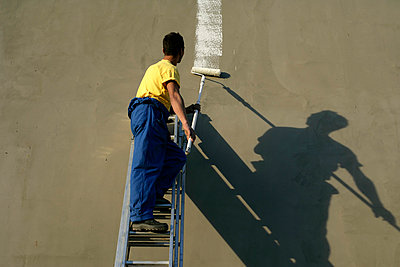 Painter painting a wall - p4903413 by STOCK4B