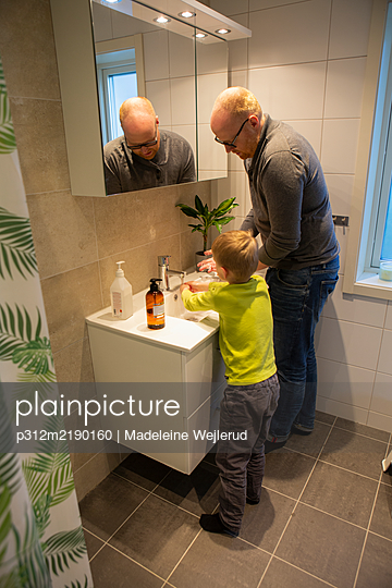 Father and son washing hands in bathroom - p312m2190160 by Madeleine Wejlerud