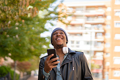 young african man in the city listening to music from his headphones - p1166m2218259 by Cavan Images