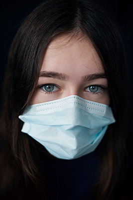 Teenage Girl with Blue Eyes in a Surgical Mask - p1617m2196493 by Barb McKinney