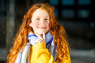 Smiling girl with hand on chin outdoors - p300m2265801 by Irina Heß