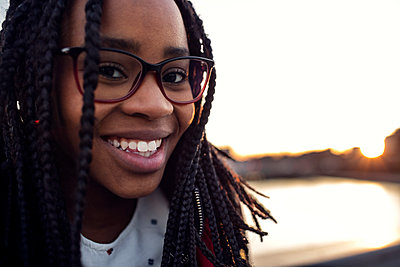 Close-up portrait of smiling teenage girl at bridge by canal against clear sky in city - p426m1179250 by Maskot