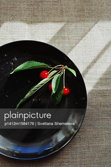 Rote Kirschen und Beeren auf einem schwarzen Teller - p1412m1584176 von Svetlana Shemeleva