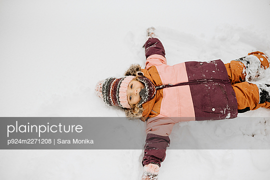 Canada, Ontario, Girl (2-3) doing snow angels - p924m2271208 by Sara Monika