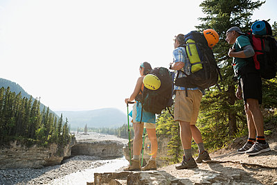 Hikers with backpacks looking at river view - p1192m1063912f by Hero Images