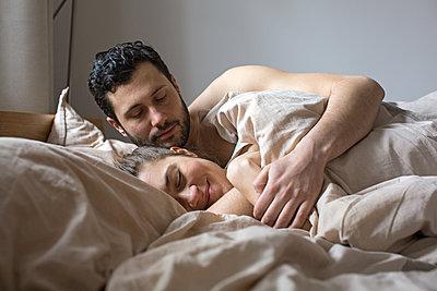 Junges Paar kuschelt im Bett  - p1301m1424739 von Delia Baum