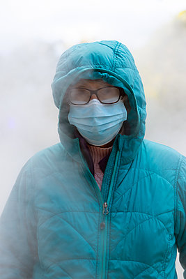 Woman in mask in foggy weather - p1614m2211829 by James Godman