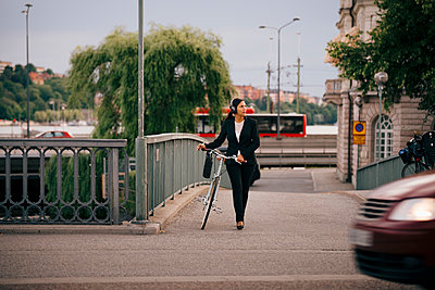 Businesswoman looking away while walking with bicycle on bridge in city - p426m2145588 by Maskot