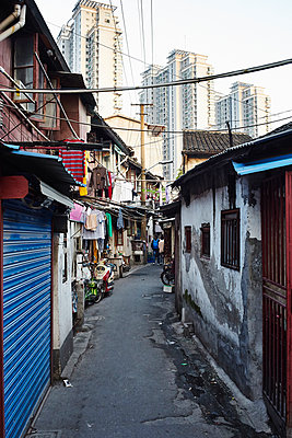 Houses in old town in front of skyscraper skyline, Shanghai, China - p429m999681 by Gu