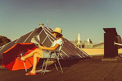 Junge Frau sitzt entspannt mit Zeitung auf Hausdach - p432m2260320 von mia takahara