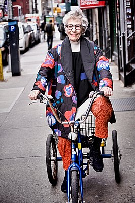 Portrait of senior woman riding tricycle - p924m1125636f by Leland Bobbe