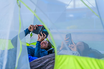 Couple in tent, reading and looking at phone - p924m2252497 by Alex Eggermont