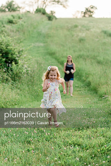 A mom and her girls walking through a meadow and picking  wildflowers. - p1166m2163039 by Cavan Images