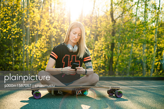 Blond woman with longboard sitting on street using smartphone - p300m1587057 von sinanmuslu